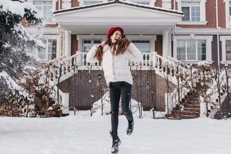 激动的年轻时髦的女人获得乐趣,跳跃在街道上的雪在冬时 长的深色的头发,红色帽子 库存图片