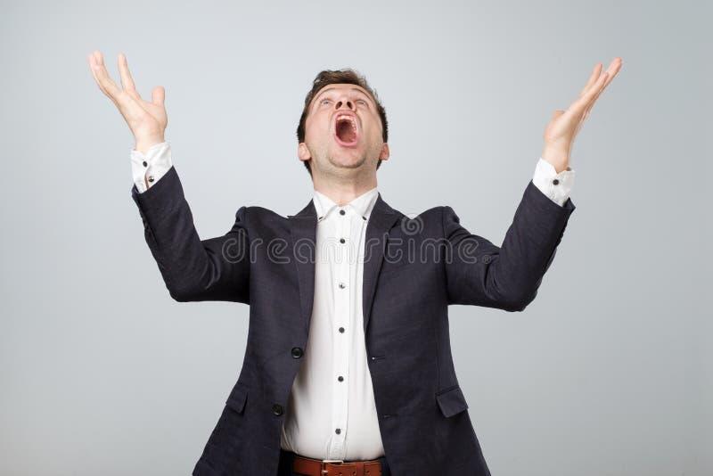 激动的年轻男性画象在衣服的尖叫在停滞手的震动和触目惊心 免版税库存图片