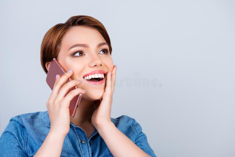激动的年轻逗人喜爱的女孩在她智能手机和微笑谈话 免版税库存图片