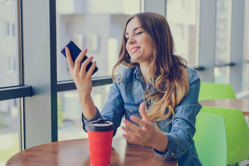 激动的微笑的愉快的妇女有休息在咖啡馆,她看notific她的智能手机电话手机的sms屏幕  免版税库存照片