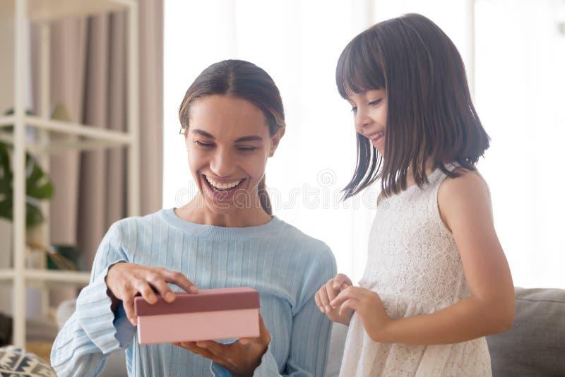 激动的快乐的从儿童daug的妈妈笑的打开的礼物盒 免版税库存图片