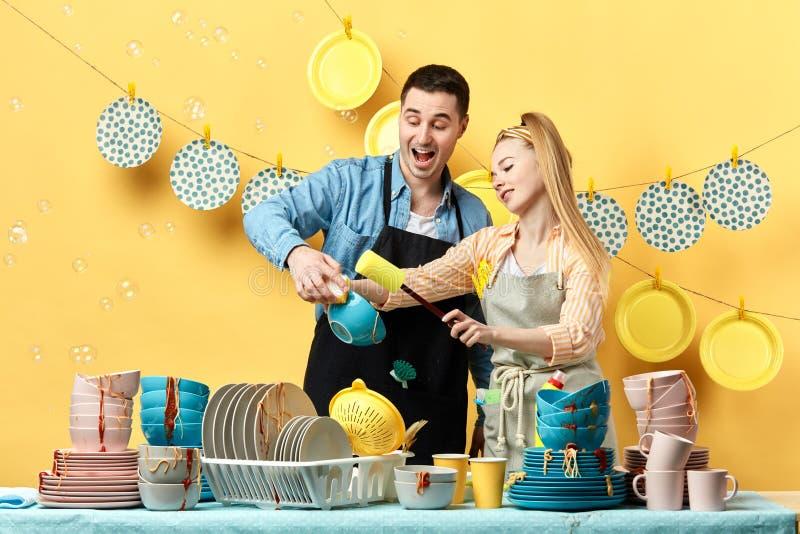 激动的快乐的夫妇洗涤的板材,肠,杯子用手 免版税库存图片