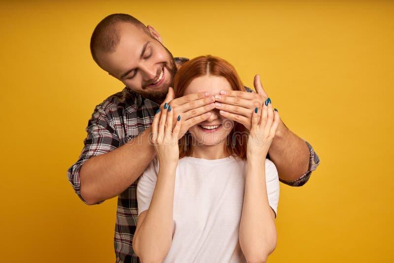 激动的快乐的年轻夫妇身分被隔绝在黄色背景,盖子眼睛,惊奇 免版税库存照片