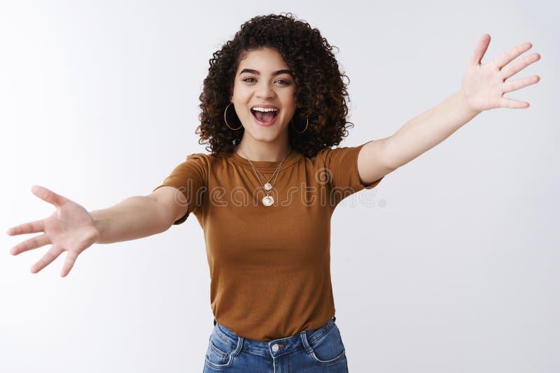 激动的愉快的可爱的时髦的现代女孩欢迎的最好的朋友传播胳膊斜向一边拥抱要愉快地拥抱发言权喂 免版税库存图片