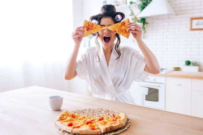 激动的愉快的年轻女人在plaing与比萨切片的厨房里 盖子眼睛用食物 非常嬉戏无忧无虑的管家 免版税图库摄影