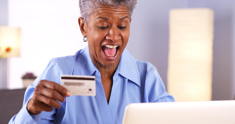 激动的成熟非洲妇女买的事在网上 免版税图库摄影