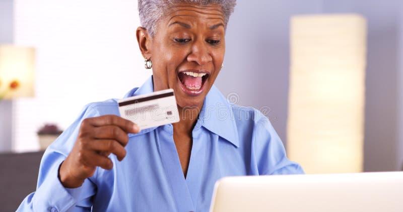 激动的成熟非洲妇女买的事在网上 免版税库存图片