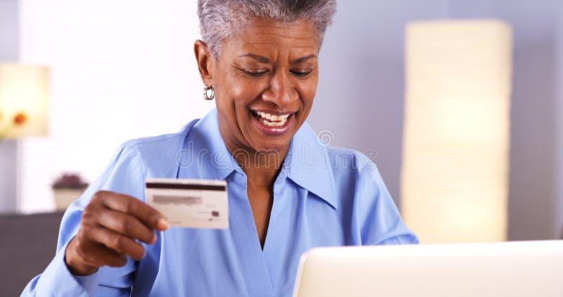 激动的成熟非洲妇女买的事在网上 免版税库存照片