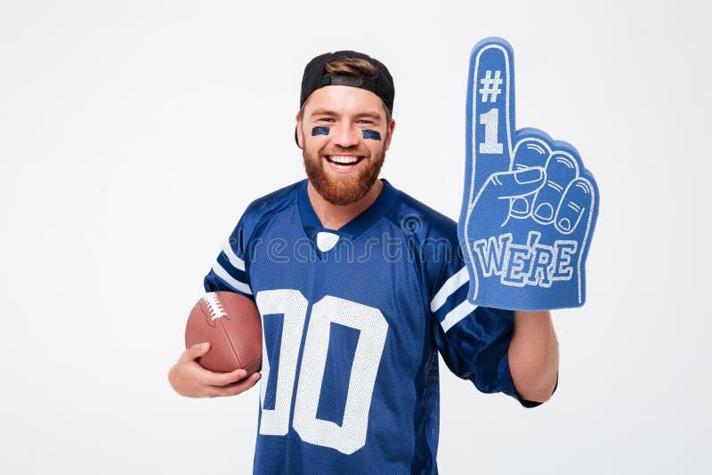 激动的拿着橄榄球球的人爱好者佩带的爱好者手套 免版税库存图片