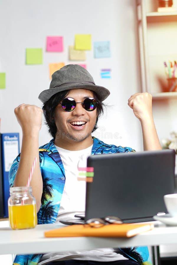激动的时髦的年轻人感到满意庆祝成功在 免版税库存照片