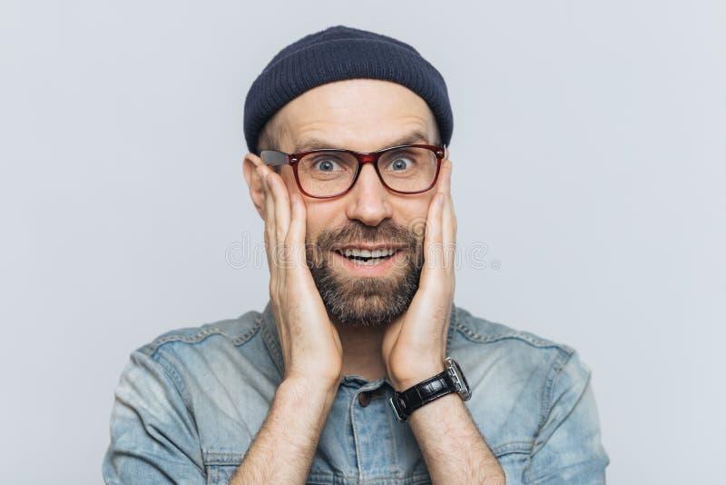 激动的有胡子的人室内射击有蓝眼睛和快乐的表示的,在时装保留在面颊的手,穿戴, 库存照片