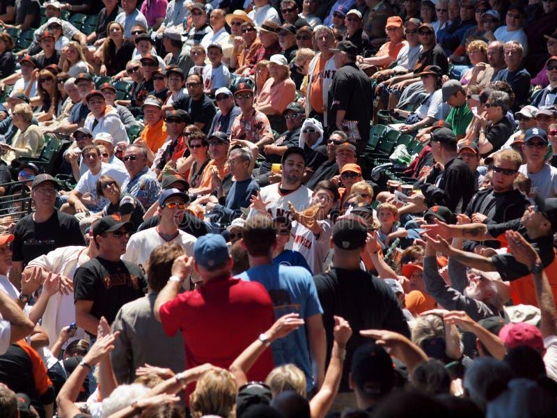 激动的爱好者到达手和手套界外球的 库存图片