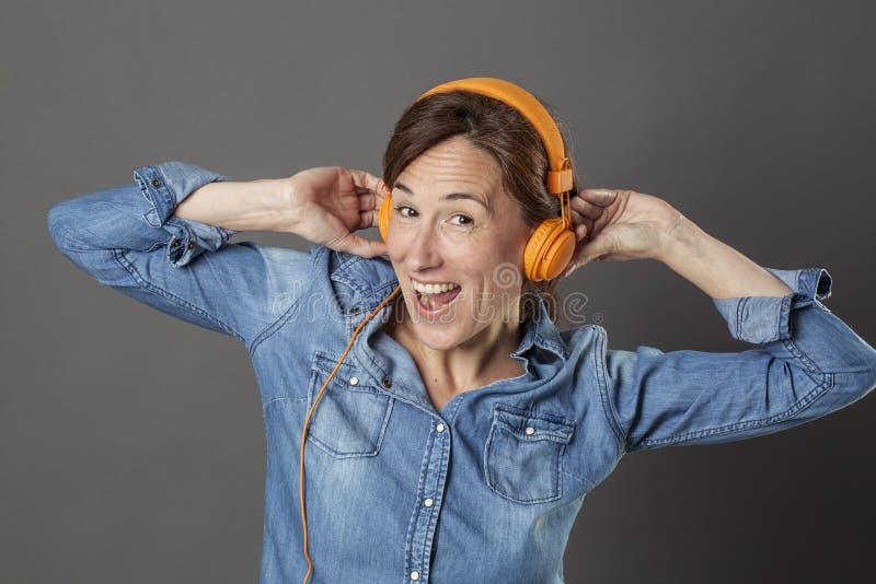 激动的美好的中部变老了笑与质朴的音乐的妇女  免版税库存图片