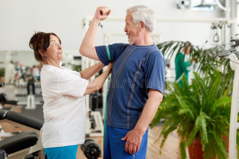 激动的老人的妇女测量的二头肌 免版税库存照片