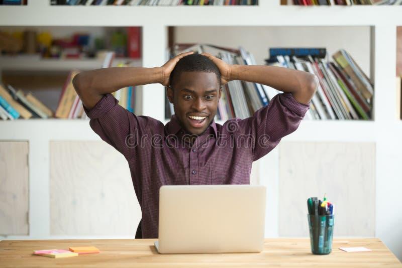 激动的黑人工作者满意对抽奖胜利 免版税图库摄影