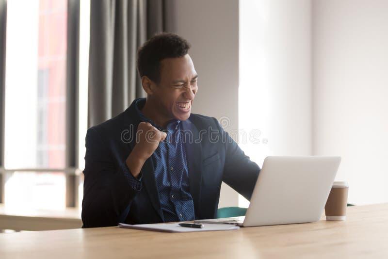 激动的黑商人感到欣快在网上读喜讯 免版税库存图片
