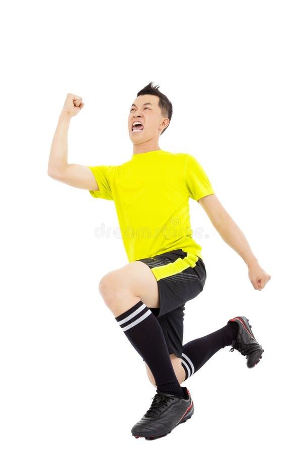 激动的年轻足球运动员培养了手和跪下来 免版税库存照片