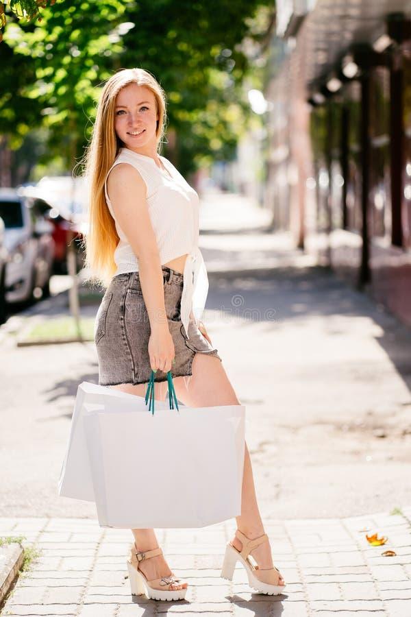 激动的shopaholic女孩藏品礼物袋子 免版税图库摄影