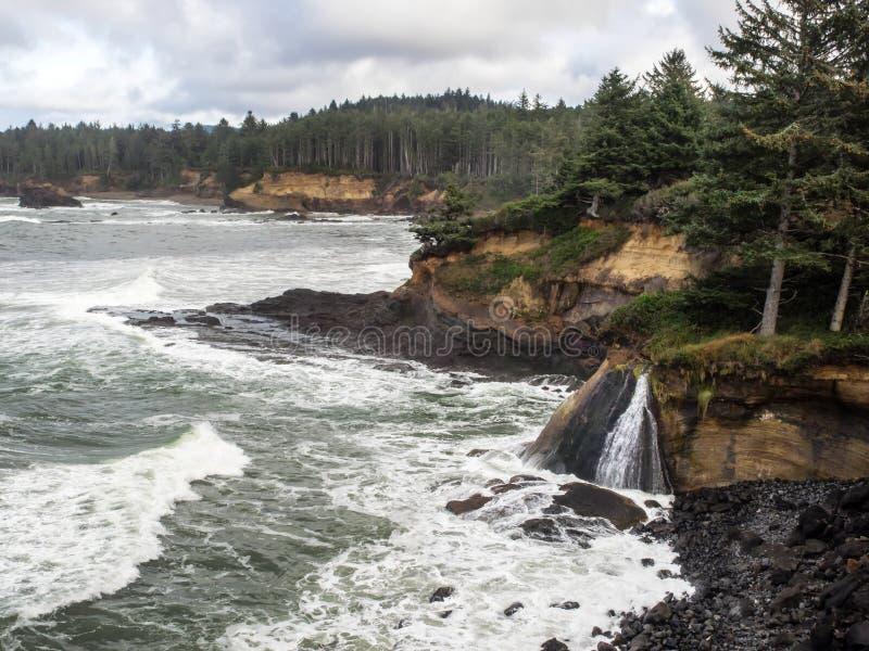 瀑布到在坚固性海岸的海浪里 免版税库存照片