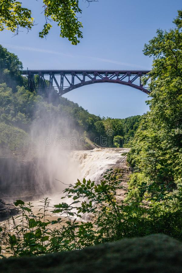 瀑布和一座铁路桥梁的图片在瀑布上 免版税库存照片