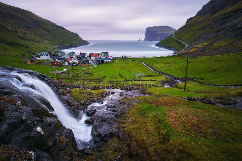 瀑布和Tjornuvik村庄在法罗岛 免版税库存照片