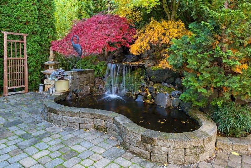 瀑布池塘在秋季期间的家庭后院 库存照片