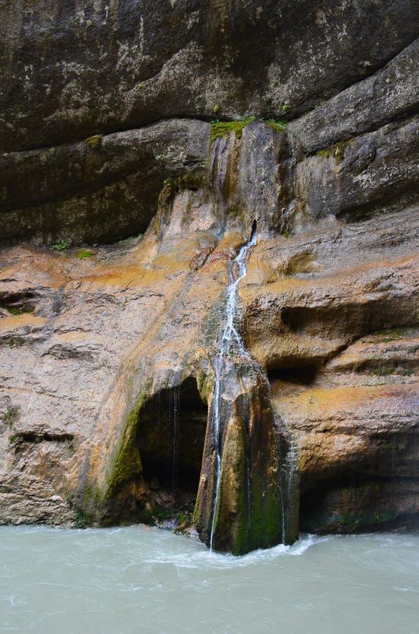 瀑布流动在岩石的一条稀薄的小河下并且落入山河 免版税库存照片