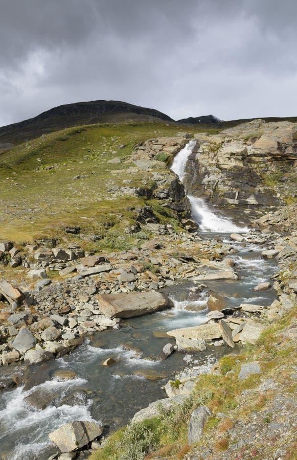 瀑布由在剧烈的滚动场面和黑暗的云彩的阳光点燃了  免版税图库摄影