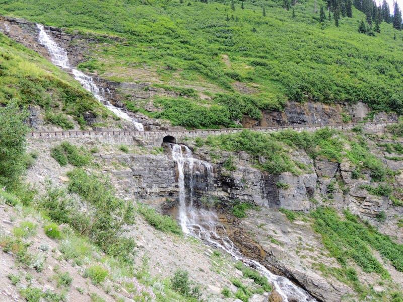 瀑布通过老岩石桥梁,沿去太阳路在冰川国家公园蒙大拿美国 库存照片