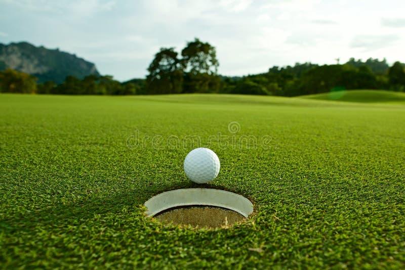火光在航路w的孔附近点燃白色高尔夫球照片  免版税图库摄影