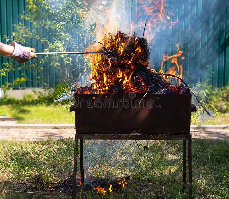 火和烟在格栅,火,火,燃烧的BBQ在围场,燃烧的干草的原因 库存图片