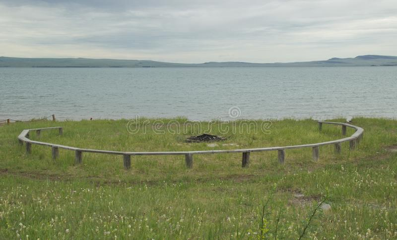 火圈子是一个长木凳在绿草的一个营火附近在夜党以后的早晨 自然视图,野餐 免版税库存照片