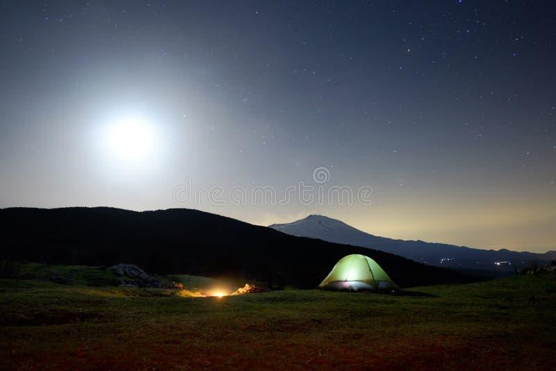 火在夜、照明设备帐篷和Etna火山里在月光下 库存照片