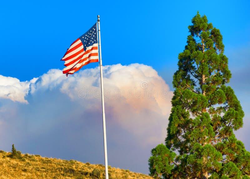 火在美国旗子后的云彩巨浪 免版税库存照片