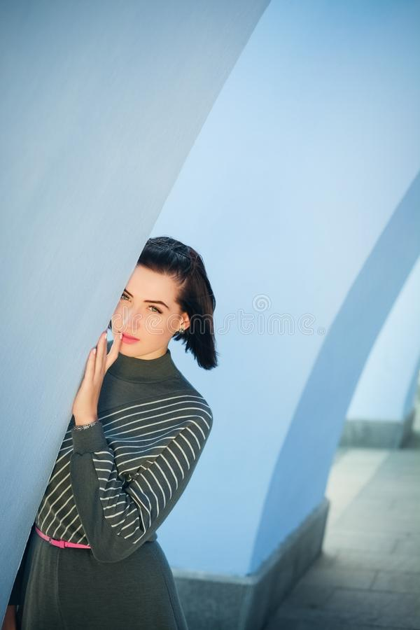 火墙壁的背景的谦虚美丽的妇女  库存照片