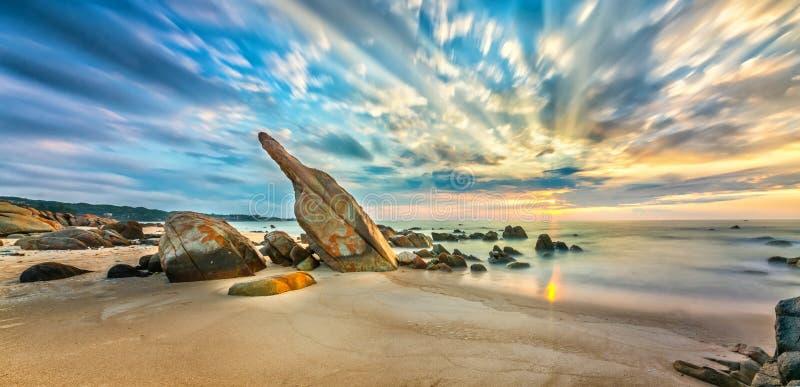 火山岩在与剧烈的天空的日出靠岸,在礁石下 免版税库存照片