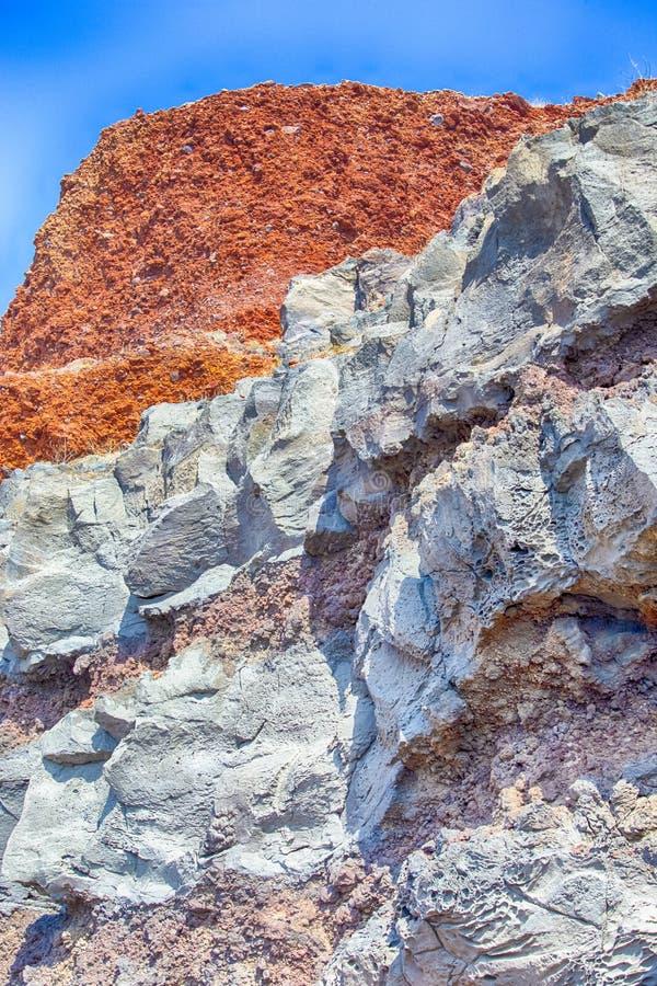 火山的破火山口混杂的岩石石灰石表面在其中一个圣托里尼海滩中 红色和白色根底 免版税库存照片