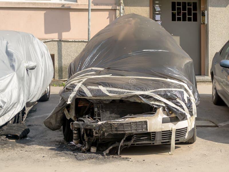火损坏的汽车在居民住房附近 部分地烧了汽车用一部黑影片盖 免版税库存图片
