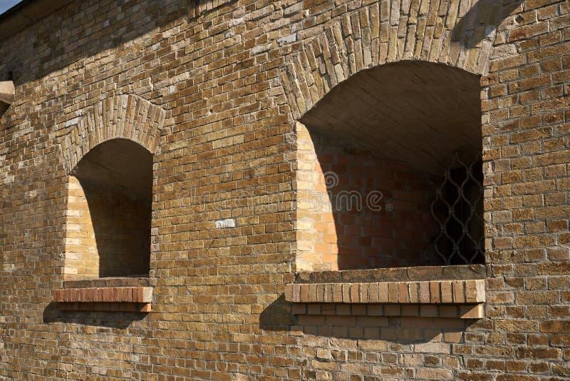 火炮的发射孔在砖墙 免版税库存照片