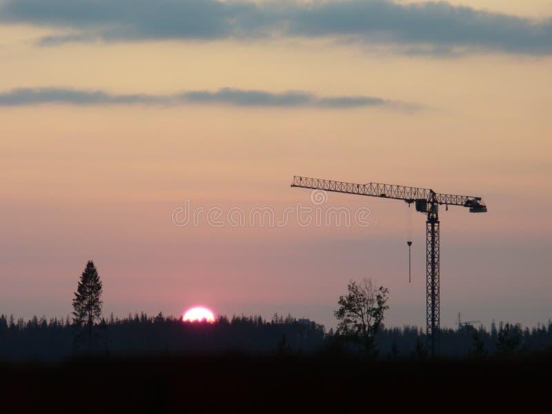 火热的日落和起重机 免版税库存照片