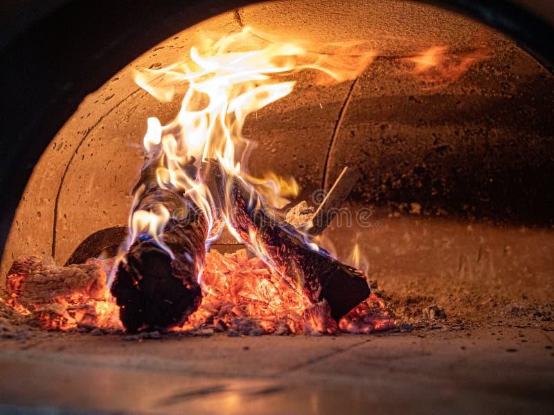 火焰,日志,灰,在木灼烧的比萨烤箱里面的炭烬 免版税库存照片