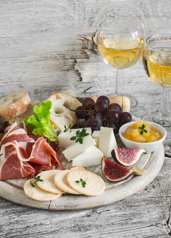 火腿、乳酪、葡萄、无花果、坚果、面包ciabatta、薄脆饼干、果酱在白色木板和两杯白葡萄酒在明亮木 库存照片