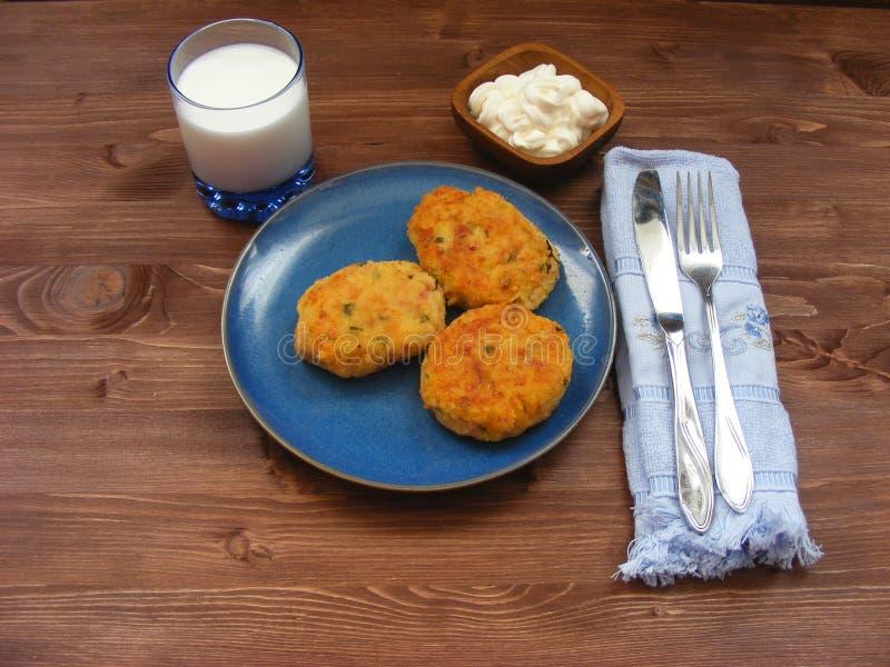 火腿、乳酪和土豆鱼圆在蓝色板材,牛奶在玻璃和酸性稀奶油在木碗在土气背景与蓝色na 库存图片