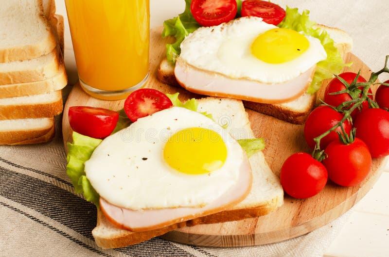 火腿三明治用炒蛋,蕃茄,莴苣,可口愈合 免版税库存照片