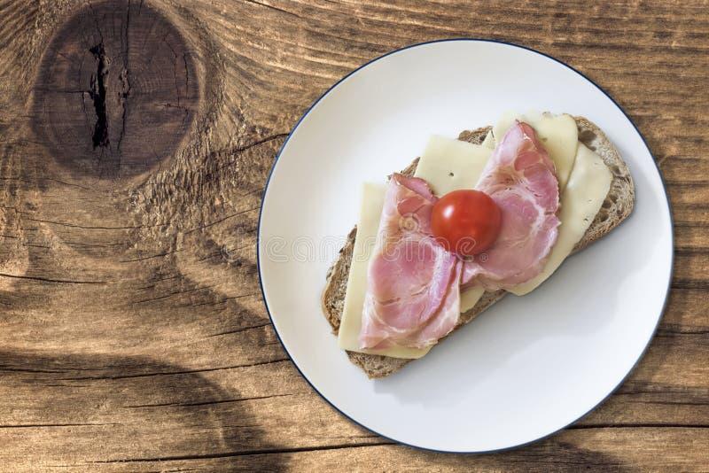 火腿乳酪和蕃茄三明治用烟肉更卤莽在木头 免版税库存照片