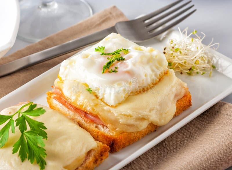火腿和乳酪三明治用熔化乳酪和煎蛋 免版税库存照片