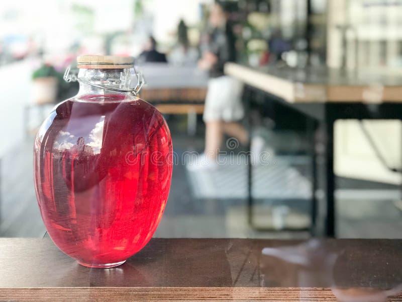 火腿,汁液,魔药,与发光的一份饮料的一家大美丽的三升玻璃银行液体与在被弄脏的bac的一个木盒盖 免版税库存照片