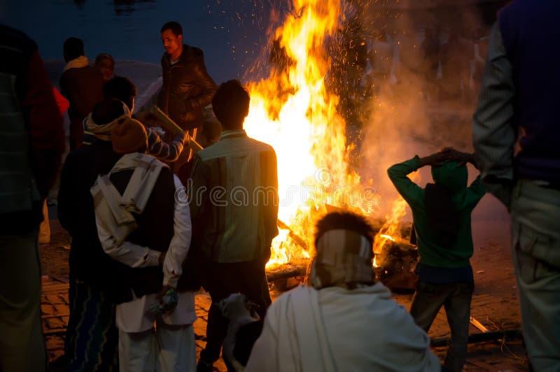 火葬仪式在恒河的Manikarnika Ghat在瓦腊纳西,人们看火葬用的柴堆 免版税库存照片