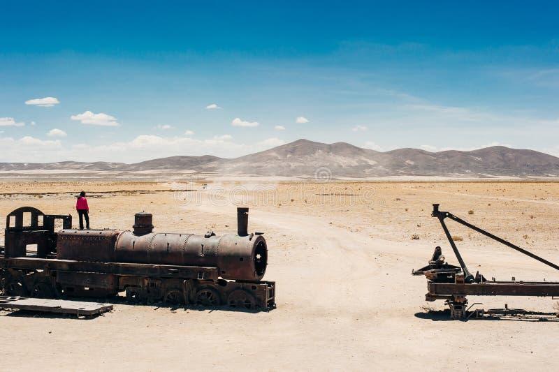 火车公墓在玻利维亚turist的乌尤尼盐沼沙漠 图库摄影