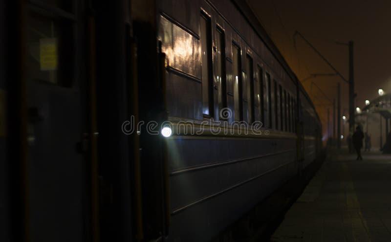 火车到达平台在晚上 明亮的光分散黑暗 库存照片